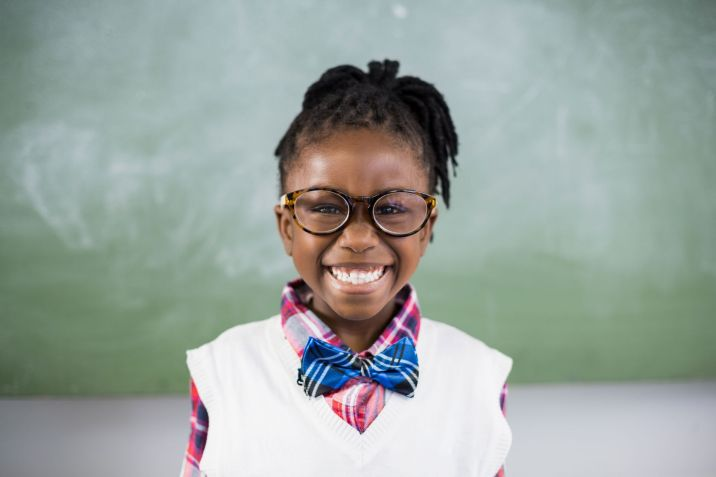 58213112 - portrait of schoolgirl smiling in classroom at school